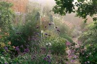 Mixed border with obelisks, Verbena bonariensis, Anemone japonica and apple tree