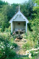 Decorative summerhouse in informal setting with Ox eye daisies at Park Farm in Essex
