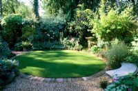 Shady garden with circular lawn, mixed planting and seating. Ladywood in Hants