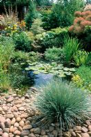 Naturalised garden pond, bank made from cobbles and pebbles