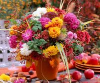 Autumnal arrangement of Chrysanthemum, Sedum, Rosa hips, Pennisetum and Rubus - In orange vase on wooden table