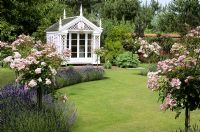 White painted summerhouse with standard Rosa 'Ballerina' at Kettle Hill