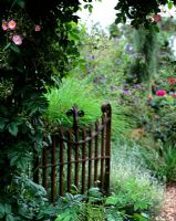 Rustic iron gate at entrance to informal cottage garden