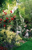 Rose covered seat with climbing roses and dog statues. Cornus controversa 'Variegata' and Rosa 'Pauls Scarlet'. Chelsea FS 1997