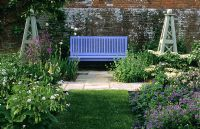 Blue bench on path with obelisks framed by borders at Broomers Hill House, Sussex