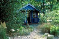 Painted blue wooden summerhouse in Bamboo and grasses garden with pebbles and wooden path.