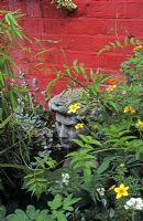 David sculpture in border with Jasminum,  Coreopsis, Helichrysum and Bamboo in pots against red wall