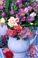 Late summer floral arrangement in blue jug - roses, hibiscus, asters, godetia and gentian