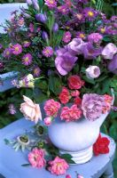 Late summer floral arrangement in blue jug on a wooden chair - roses, hibiscus, asters, godetia and gentian