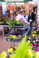 Mother and small child in plant centre with trolley selecting plants
