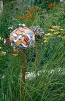 Decorative mulit-coloured mosaic balls on stakes surrounded by grasses - Crisis Garden, Hampton Court Flower Show 2005