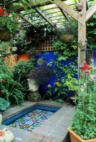 Mediterranean style courtyard garden with raised pool and blue painted wall - Loggia, Canopy, Sweet peas on obelisk in container -Brighton