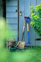 Spade and fork leaning up against blue wooden shed