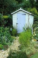 Gravel path leading to painted shed in seaside themed garden with Yuccas and phormium. Decorative use of painted spades.