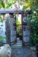 Wood and metal oriental ornate gates leading to Cevan Forristt's garden in San Jose, California