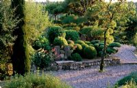 Clipped pine trees on terrace above stone wall - La Chabaude, France