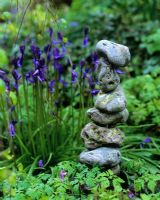 Sculpture made from a pile of stones with Hyacinthoides non-scripta - bluebells in background