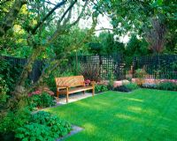 Wooden bench with angular formal lawn, terracotta pink rendered walls, Malus, Phormium tenax 'Purpureum', Sedums, Verbena bonariensis