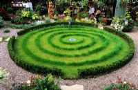 Circular lawn with spiral mown pattern in a decorated garden - Chester