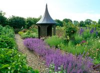 Willow summerhouse with lead covered roof in cottage garden with willow fences and raised beds, Nepeta 'Walker's Low', Delphiums, roses, Persicaria bistorta 'Superba' and Alliums