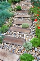 A driftwood path leading to door with Papaver rhoeas, Thymus, Erigeron and Festuca glauca
