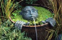 Wooden half barrel pond with spitting man fountain by Dennis Fairweather