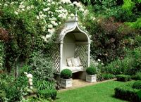 Classic gazebo with bench and cushions in formal garden. Rosa 'Kiftsgate', Teucrinum, Cotinus, Buxus sempervirens - Box topiary balls