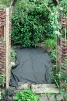 Laying down weed suppressant fabric over neglected path in need of repair, viewed through willow archway. Corylus avellana 'Contorta' in background.