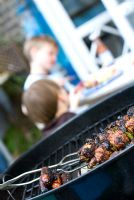 Barbecue with children in the background