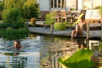 Couple enjoying swimming pond on warm summer's evening with decking and seating in background - Bressingham, Norfolk.