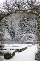 Buxus hedges surrounded by a clipped hedge Carpinus betulus, hornbeam gateway, - The Renaissance garden with snow, large pine trees at the entrance, the gardens of Norrviken
