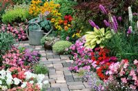 Bright and breezy summer bedding plants flank a cottage garden style path with an old watering can as a focal point. Petunias, Ageratum, busy Lizzies, Rudbeckias, fibrous rooted Begonias and Lobelia carpet around Hostas and Liatris