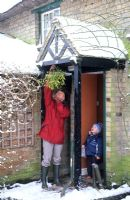 Mother and child hanging up Mistletoe