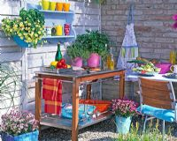 Outdoor kitchen with container planting of Pelargonium 'Angeleyes', Levisticum, Thymus, Ocimum and Calibrachoa