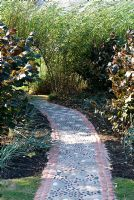 Path with a daisy design made from pebbles and stones set in coloured concrete leading to a willow tunnel with Corylus avelana 'Purpurea' and grasses on either side