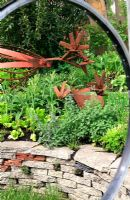 Garden built from recycled materials - Windows made from bicycle wheels, chicken sculptures made from old mower parts and underplanted with vegetables and herbs