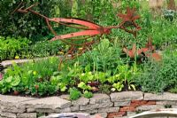 Ornamental kitchen garden with a chicken sculpture made from recycled machinery parts and retaining walls of salvaged concrete slabs and roof tiles