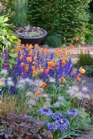 The Bupa Garden designed by Cleve West, RHS Chelsea 2008 with Geum 'Fire Opal', Pulsatilla vulgaris, Scilla peruviana and Hedge of Carpinus betulus - Hornbeam