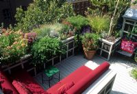 Small urban roof garden with wooden decked patio and corner bench seat with red cushions - New York, USA