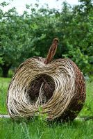 Woven willow apple sculpture in an orchard - RHS Gardens Wisley