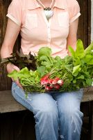Seated woman holding a rustic basket of freshly cropped salad produce