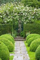 Formal garden with wooden pergola and climbing Rosa 'New Dawn', clipped Taxus and Buxus hedging with view to stone statue