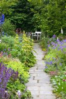 Mixed summer borders of Delphiniums, Phlomis russeliana, Alchemilla mollis, Nepeta 'Walker's Low', Geranium 'Johnson's Blue' and Centranthus ruber leading to seating area