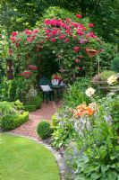 Seating area under pavillon with climbing rose