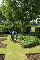 Copper seed pod in vegetable garden by Carrie Norman, plantings of potatoes in horseshoe beds - Lucy Redman's School of Garden Design