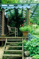 Garden in August with steps leading up to a blue painted summer house, designed by Alan Titchmarsh at Barleywood, Hampshire