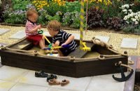 Children playing in a sand pit shaped like a boat