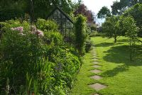 Simple paving slab path runs alongside the greenhouse, beside small orchard in private garden, Hampshire.