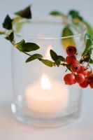 Christmas candle decorated with Vinca minor foliage and Cotoneaster berries