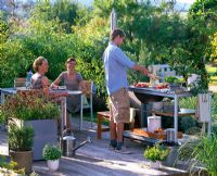 People in outdoor kitchen with pots with Origanum, Rosmarinus, Mentha and Laurus.